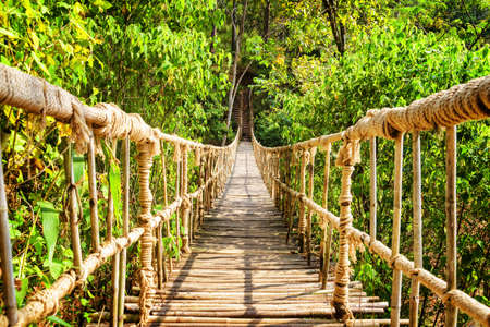 Scenic simple suspension bridge over gorge. Amazing footbridge made from rope and bamboo. Beautiful hanging bridge among green woods.