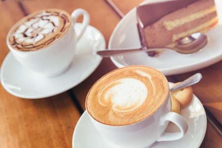 Due tazze di caffè caldo Cappuccino e torta di mousse al cioccolato sul tavolo di legno al caffè. Bevande fresche e dessert dolci. Focus sulla prima tazza. Immagine tonica.