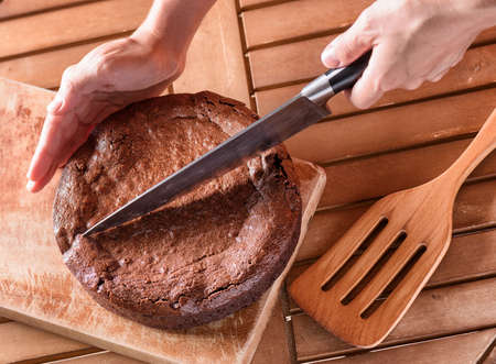 trozo de pastel: Vista superior del cuchillo de la explotación agrícola de la mano y del corte del pastel de brownie recientemente cocido al horno en la tabla de madera. Hecho en casa delicioso postre de chocolate dulce, comida familiar.