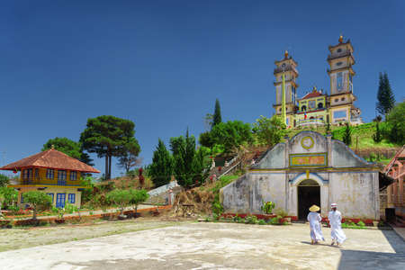 adherents: Towers of the Thanh That Da Phuoc on blue sky background. Scenic view of the temple for the Cao Dai religion adherents at Dalat (Da Lat), Vietnam. Dalat is a popular tourist destination of Asia.