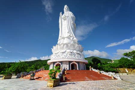 Majestic view of the Lady Buddha (the Bodhisattva of Mercy) at the Linh Ung Pagoda, Danang (Da Nang), Vietnam. White Buddha statue on blue sky background.