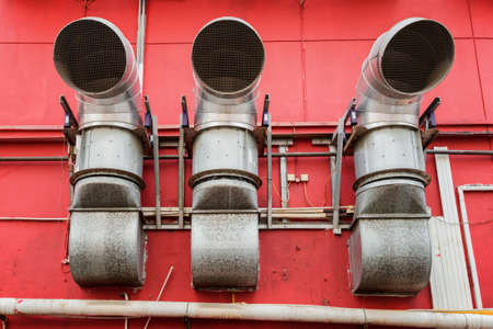 venting: Ventilation pipes outside a red building. View of urban venting system. Industrial concept. Stock Photo