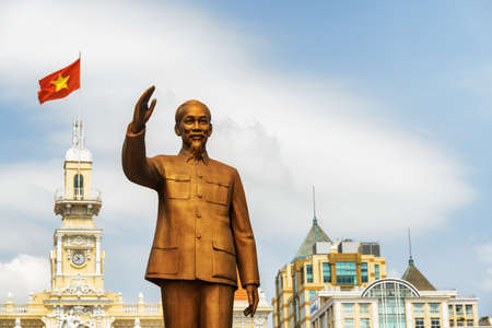 Ho Chi Minh City, Vietnam - February 23, 2017: Bronze statue of President Ho Chi Minh on square of the same name. The flag of Vietnam (red flag with a gold star) fluttering on the City Hall building.