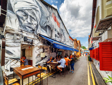 Singapore - February 19, 2017: Tourists having a lunch in street cafe at Haji Lane. Decorative painted wall of old house. Street art at the Muslim quarter (Arab quarter). Graffiti in Singapore.