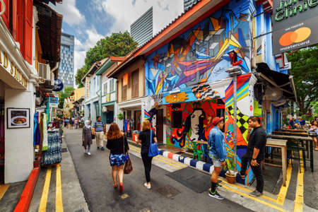 Singapore - February 19, 2017: Tourists walking along gift shops at Haji Lane. Decorative painted wall of old house. Amazing street art at the Muslim quarter (Arab quarter). Graffiti in Singapore. 新闻类图片