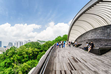 Singapore - February 19, 2017: Tourists walking on the Henderson Waves. Amazing pedestrian wooden bridge curving and leading to a green park. Beautiful cityscape.