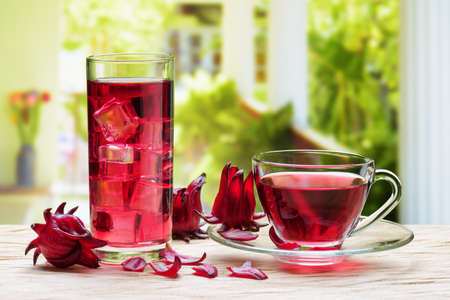 Cup of hot hibiscus tea (karkade, Agua de flor de Jamaica) and the same cold drink with ice cubes in glass on wooden table at terrace. Drink made from magenta calyces (sepals) of roselle flowers. 版權商用圖片 - 78010856