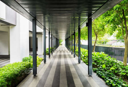 Modern open corridor protecting from the sun and rain. Outside walkway along a building.