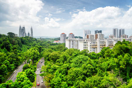 Beautiful summer cityscape in Singapore. Modern buildings and road among green trees. Park in residential area. Amazing skyscrapers and the sea are visible in background. 免版税图像