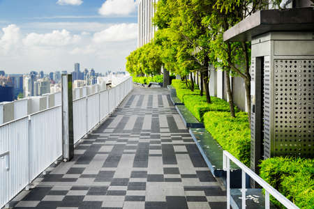 public housing: Beautiful rooftop garden. Outside terrace with scenic park and amazing city view. Modern benches under green trees along walkway. Urban eco design and mini-ecosystem. Landscaping in Singapore.