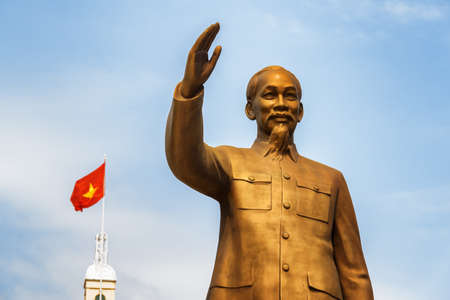 Ho Chi Minh City, Vietnam - February 23, 2017: Bronze statue of President Ho Chi Minh. The flag of Vietnam (red flag with a gold star) is visible on blue sky background.
