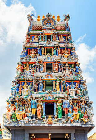 Singapore - February 17, 2017: The gopuram of Sri Mariamman Temple on blue sky background. Amazing colorful monumental entrance tower of the oldest Hindu temple at Singapore.