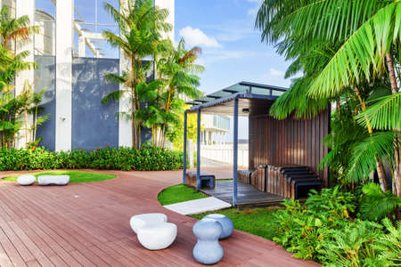 Beautiful rooftop garden. Outside terrace with amazing park. Modern wooden arbor among green trees. Urban eco design and mini-ecosystem. Stockfoto