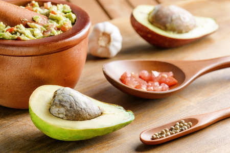 Closeup view of avocado and fresh homemade Guacamole in wooden mortar with pestle (molcajete). Traditional Mexican sauce from ripe avocados. Healthy vegetarian eco food.