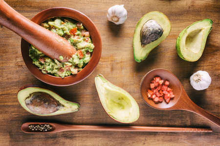 Top view of fresh homemade Guacamole in wooden mortar with pestle (molcajete). Traditional Mexican sauce from ripe avocados on wooden table. Healthy vegetarian food.