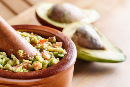 Closeup view of fresh homemade Guacamole in wooden mortar with pestle (molcajete). Traditional Mexican sauce from ripe avocados on wooden table. Healthy vegetarian eco food.