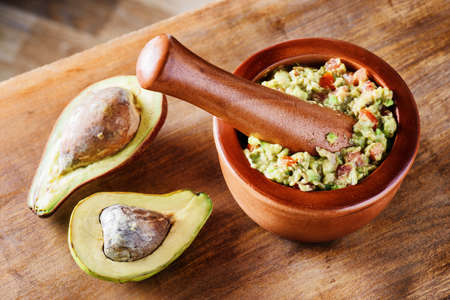 Top view of homemade Guacamole in wooden mortar with pestle (molcajete). Traditional Mexican sauce from fresh ripe avocados on wooden table. Healthy vegetarian eco food. Stock Photo