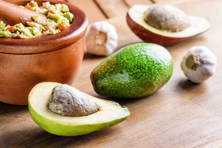 Closeup view of avocados and fresh homemade Guacamole in wooden mortar with pestle (molcajete). Traditional Mexican sauce from ripe avocados. Healthy vegetarian eco food. Stock Photo