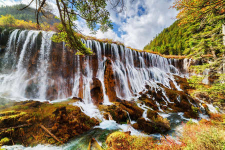 Fantastic view of the Nuo Ri Lang Waterfall (Nuorilang) among colorful fall woods in Jiuzhaigou nature reserve (Jiuzhai Valley National Park) of Sichuan province, China. Amazing autumn landscape. Kho ảnh