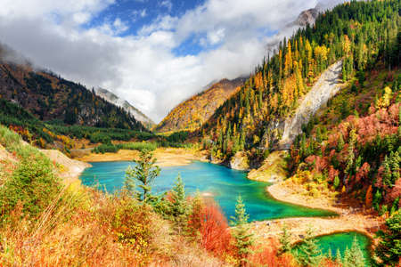 Fantastic view of the Upper Seasonal Lake with azure water among colorful fall woods and mountains in fog, Jiuzhaigou nature reserve (Jiuzhai Valley National Park), China. Sunny autumn landscape.