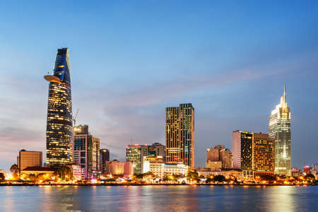 Ho Chi Minh City skyline and the Saigon River at sunset. Wonderful view of skyscraper and other modern buildings at downtown. Ho Chi Minh City is a popular tourist destination of Vietnam. Stockfoto