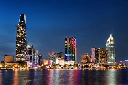 호치민 시티 스카이 라인과 사이공 강. 마천루와 시내에서 다른 현대적인 건물의 놀라운 화려한 야경. 호치민시는 베트남의 인기있는 관광지입니다. 스톡 콘텐츠