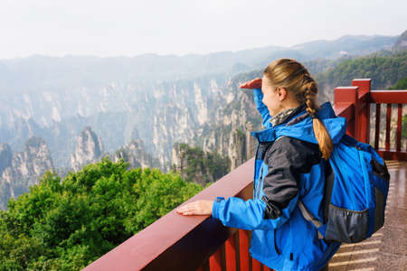 Young female tourist with blue backpack enjoying beautiful mountain view in the Zhangjiajie National Forest Park, Hunan Province, China. Her hair braided in French plait. Outdoor portrait. Stock Photo