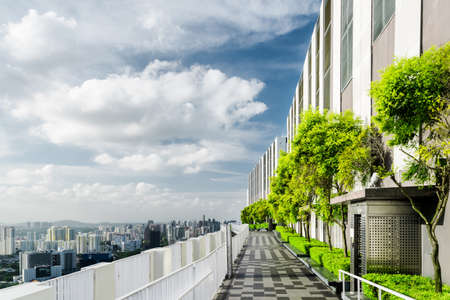 balcony: Amazing rooftop garden. Scenic outside terrace with park and beautiful city view. Modern benches under green trees along walkway. Urban eco design and mini-ecosystem. Landscaping in Singapore. Stock Photo