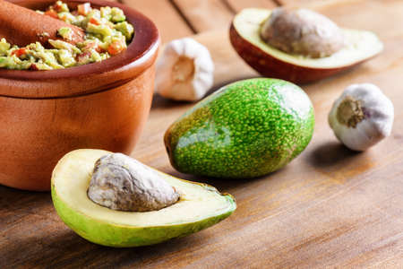 Closeup view of avocados and fresh homemade Guacamole in wooden mortar with pestle (molcajete). Traditional Mexican sauce from ripe avocados. Healthy vegetarian food.