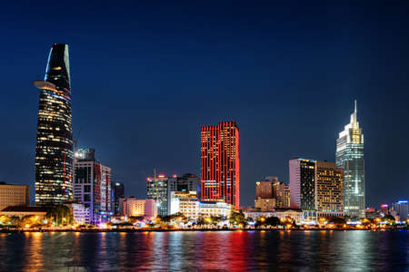 Ho Chi Minh City skyline and the Saigon River. Scenic colorful night view of skyscraper and other modern buildings at downtown. Ho Chi Minh City is a popular tourist destination of Vietnam. Stock Photo