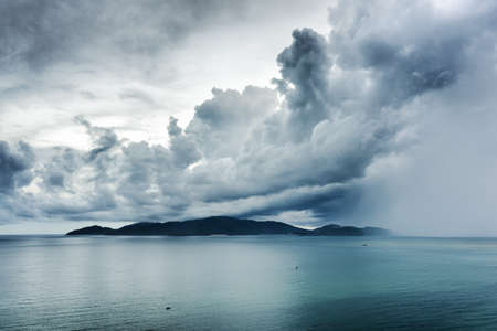 Wonderful seascape with dramatic stormy sky. Rain is visible at right. Scenic view of Nha Trang Bay, the South China Sea, Vietnam. Stock Photo
