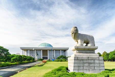 Korean lion dog statue on green lawn in front of the National Assembly Proceeding Hall, Seoul. The building serves as the location of the legislative branch of the South Korean national government.