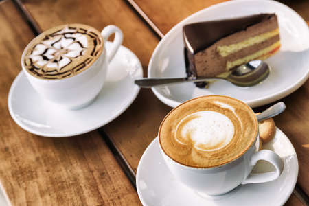 Two cups of Cappuccino coffee and chocolate mousse cake on wooden table at cafe. Fresh invigorating drink and sweet dessert. Stock Photo
