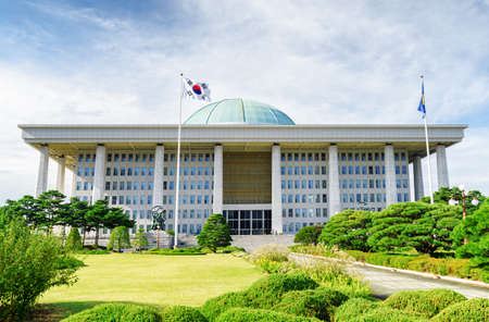 Scenic view of the National Assembly Proceeding Hall at Seoul in the Republic of Korea. The building of the South Korean national government. The flag of the South Korea on blue sky background. Editorial
