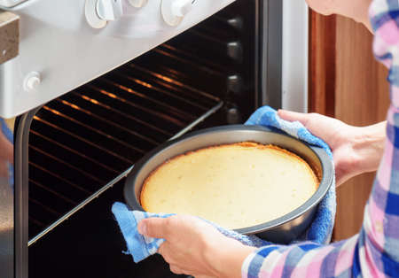 Closeup view of housewife taking cheesecake out of oven in kitchen. Young woman wearing colorful checkered shirt.