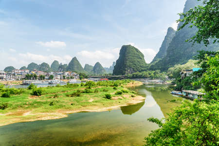 Beautiful view of the Li River (Lijiang River) and Yangshuo Town among karst mountains on sunny day. Amazing landscape at Yangshuo County of Guilin, China. Tourist boats are visible on the river.
