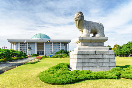 View of Korean lion dog statue on lawn in front of the National Assembly Proceeding Hall, Seoul. The building serves as the location of the legislative branch of the South Korean national government.