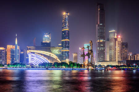 Night view of skyscrapers and other modern buildings at the Tianhe District of the Zhujiang New Town in Guangzhou, China. Colorful city lights reflected in water of the Pearl River. Guangzhou skyline.