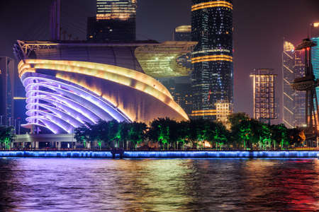 Wonderful night view of modern buildings at the Tianhe District of the Zhujiang New Town in Guangzhou, China. Beautiful colorful city lights reflected in water of the Pearl River. Amazing cityscape.