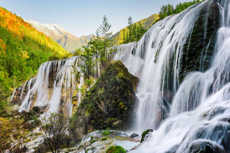 Beautiful view of the Pearl Shoals Waterfall among scenic wooded mountains and evergreen forest in Jiuzhaigou nature reserve (Jiuzhai Valley National Park), China. Amazing autumn landscape at sunset. Stockfoto