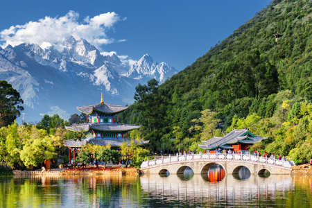 Amazing view of the Jade Dragon Snow Mountain and the Black Dragon Pool, Lijiang, Yunnan province, China. The Suocui Bridge over pond and the Moon Embracing Pavilion in the Jade Spring Park.