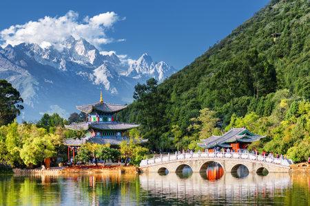 Vista stupefacente di Jade Dragon Snow Mountain e Black Dragon Pool, Lijiang, provincia dello Yunnan, Cina. Il ponte Suocui sul laghetto e il Moon Embracing Pavilion in Jade Spring Park. Archivio Fotografico - 93497060