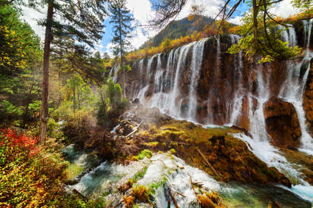 Amazing view of the Nuo Ri Lang Waterfall (Nuorilang) among colorful fall woods in Jiuzhaigou nature reserve (Jiuzhai Valley National Park) of Sichuan province, China. Fantastic autumn landscape.