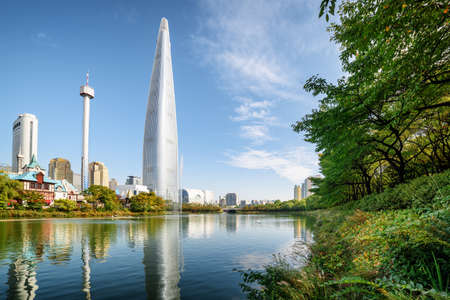 Beautiful lake among green trees in scenic park at downtown of Seoul, South Korea. Skyscraper is visible on blue sky background. Modern tower reflected in water. Sunny cityscape.