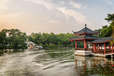 Amazing view of traditional Chinese pavilion by lake in park at sunset. Beautiful summer landscape in Guilin, China. White marble bridge and tourist boat are visible in background. Editorial