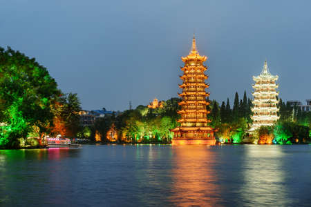 Amazing view of the Sun and Moon Twin Pagodas at Shanhu Lake (Fir Lake) at dusk. Gold and Silver Pagodas illuminated at downtown of Guilin, China. Guilin is a popular tourist destination of Asia.