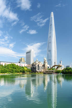 Amazing view of white skyscraper reflected in lake at downtown of Seoul, South Korea. Wonderful cityscape with modern tower on blue sky background. Seoul is a popular tourist destination of Asia.