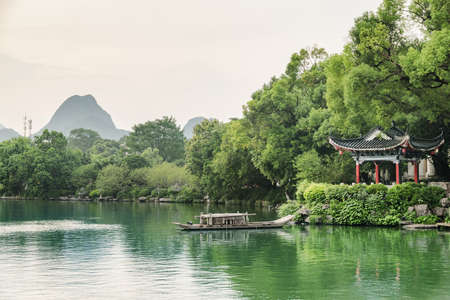 Amazing evening view of traditional Chinese pavilion by lake in park of Guilin, China. Beautiful summer landscape. Guilin is a popular tourist destination of Asia.