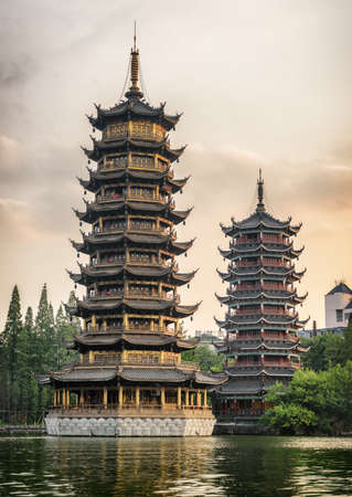 The Sun and Moon Twin Pagodas at Shanhu Lake (Fir Lake) in downtown of Guilin in China at sunset. Guilin is a popular tourist destination of Asia.
