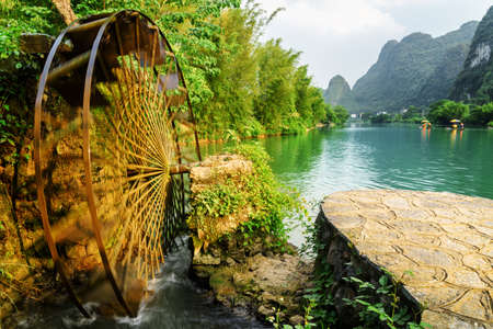 Amazing moving water wheel (noria) on the Yulong River in Yangshuo County of Guilin, China. Scenic karst towers are visible in background. Yangshuo County is a popular tourist destination of Asia. Foto de archivo